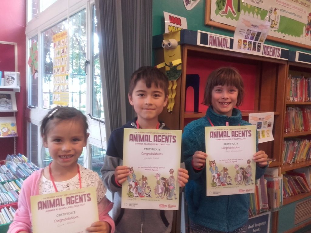 Photograph of three children collecting certificates.